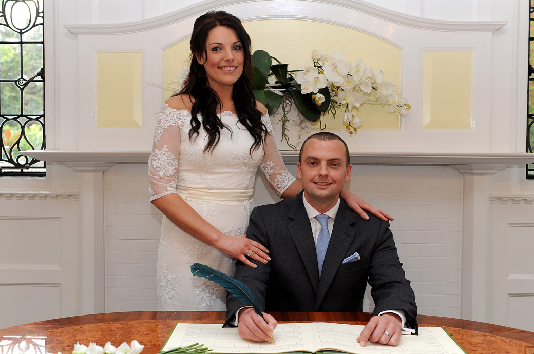 A smiling husband and wife pose signing the marriage register in this traditional wedding photograph taken in the popular Surrey wedding venue Sutton Register Office