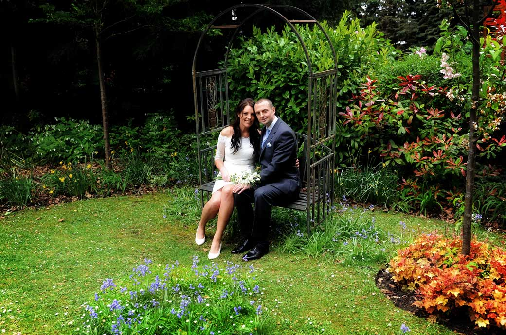 A sweet wedding photograph of a happy husband and wife taken as they sit together all alone on an ornate metal garden seat at Surrey wedding venue Sutton Register Office