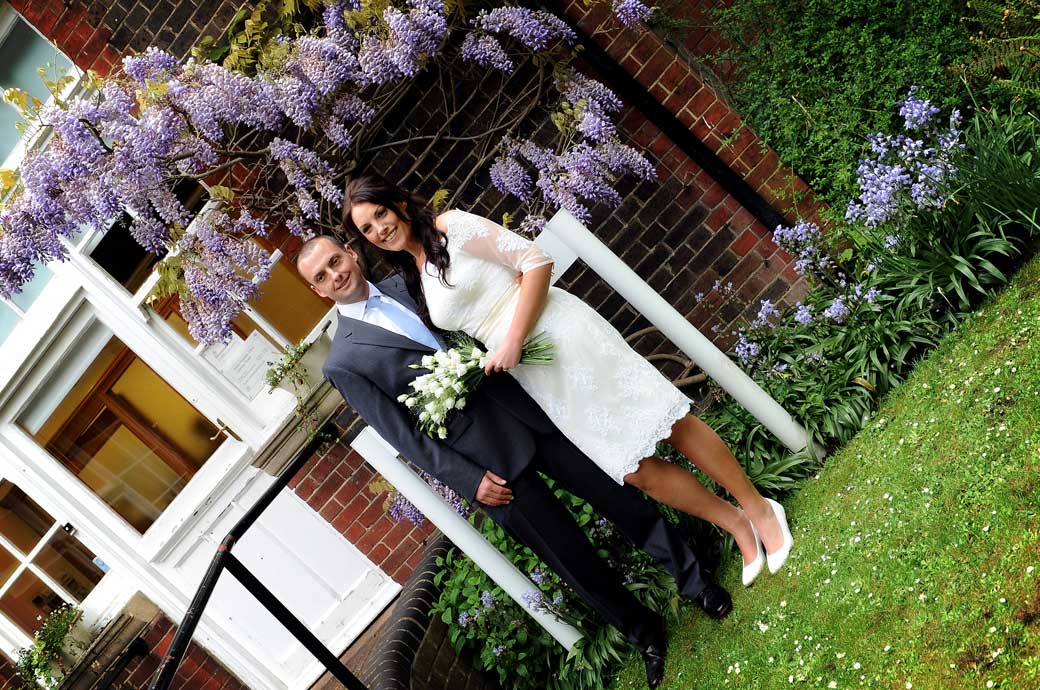 Smiling happy newly-weds wedding picture taken by the pretty wisteria by the office door to Sutton Register Office a popular and intimate Surrey wedding venue