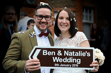 Fun wedding photograph of the Bride and groom covered in confetti and holding a road sign announcing their marriage at  Surrey wedding venue Sutton Register Office