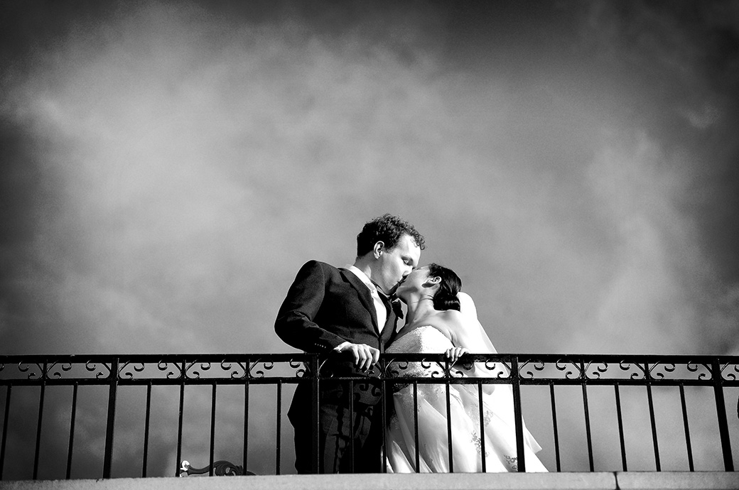Romantic wedding photograph taken on the River room balcony at Surrey wedding venue The Petersham Hotel in Richmond as they kiss against a moody sky