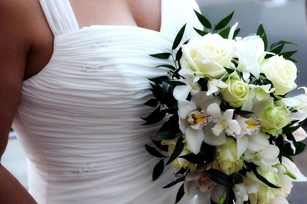 Bride's beautiful wedding dress and fresh flower bouquet captured in this zoomed in wedding photo from the smart and popular Surrey wedding venue The Petersham Hotel in Richmond