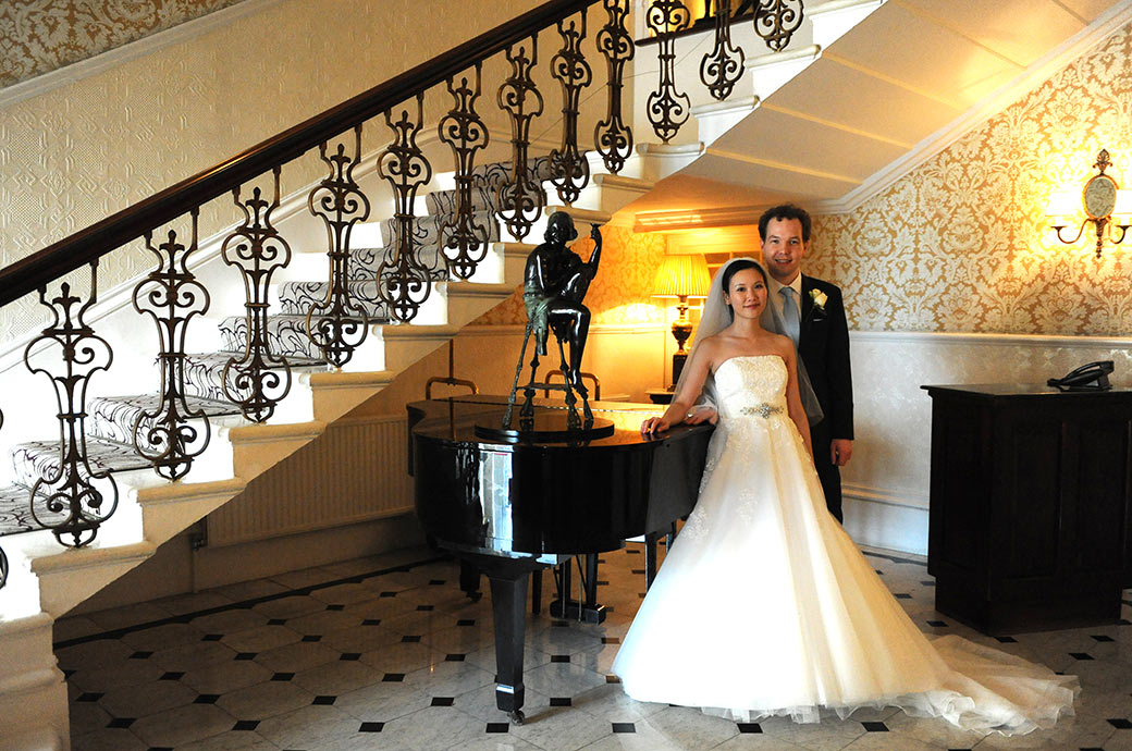 Happy and content Bride and Groom pose by the piano in the hall below the grand staircase at Surrey wedding venue The Petersham Hotel just off Richmond Hill