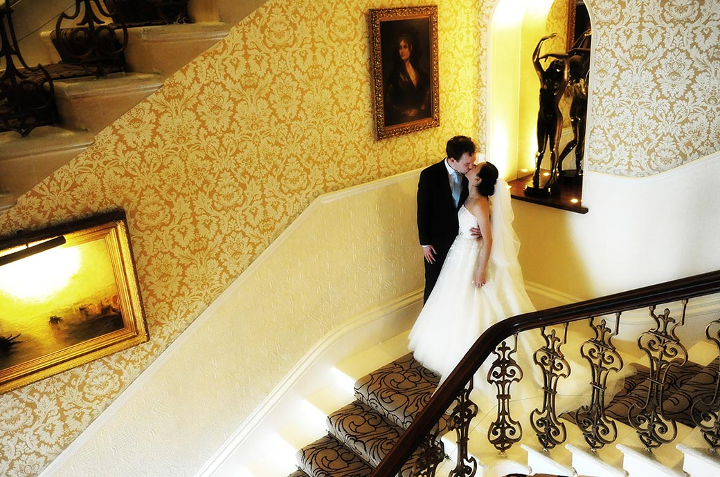 Romantic wedding picture of a newlywed couple at the grand Surrey wedding venue The Petersham Hotel in Richmond kissing on the stairs