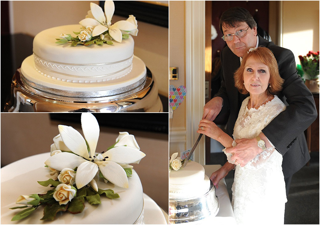 Bride and groom cut their white wedding cake in the River Room at the grand Petersham Hotel a Surrey wedding venue located in Richmond with wonderful views over The Thames