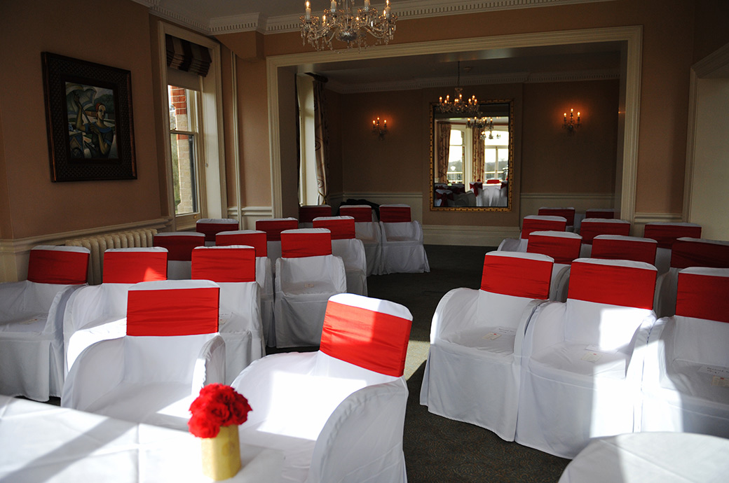 The intimate River Room at Surrey wedding venue The Petersham Hotel in Richmond dressed for a marriage service with white and red chair covers