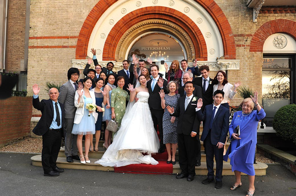 All the wedding guests stand with the bride and Groom on the front steps to The Petersham Hotel a fine grand Surrey wedding venue in Richmond