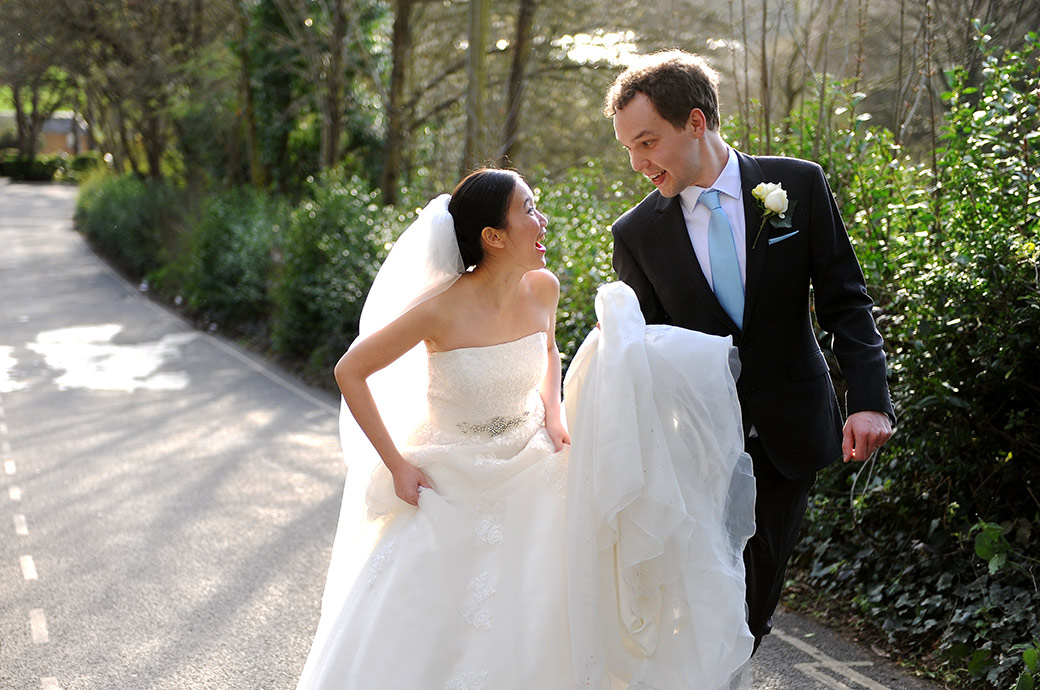 All fun smiles love and excitement for the young newlyweds as they walk up Nightingale Lane after getting married at Surrey wedding venue The Petersham Hotel