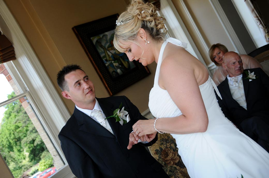 The Groom watches his Bride place on the wedding ring captured at The Petersham Surrey wedding venue in the River Room