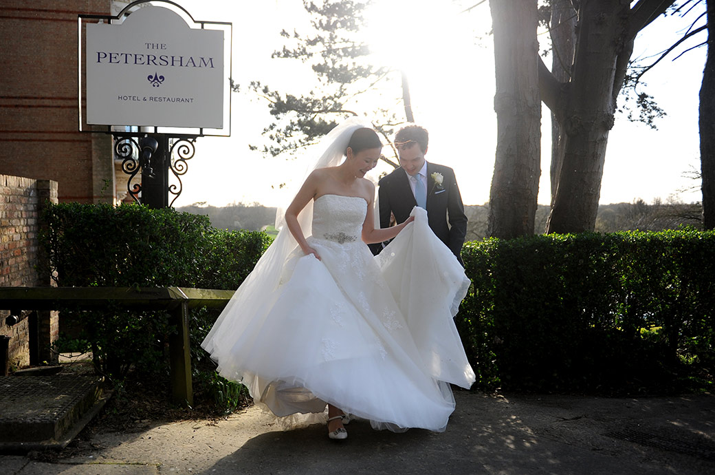 Groom helps Bride with wedding dress as they leave Surrey wedding venue The Petersham Hotel in Richmond to walk up Nightingale lane up to the Terrace Walk