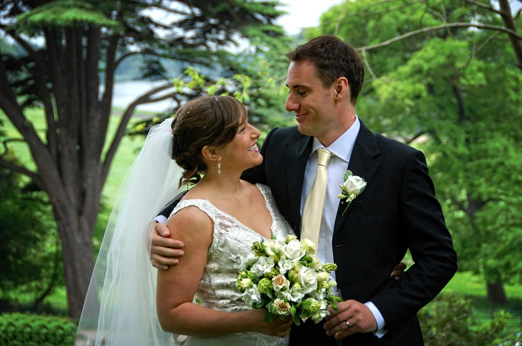 A happy loving look between the Bride and Groom as they embrace in the garden at Surrey wedding venue The Petersham