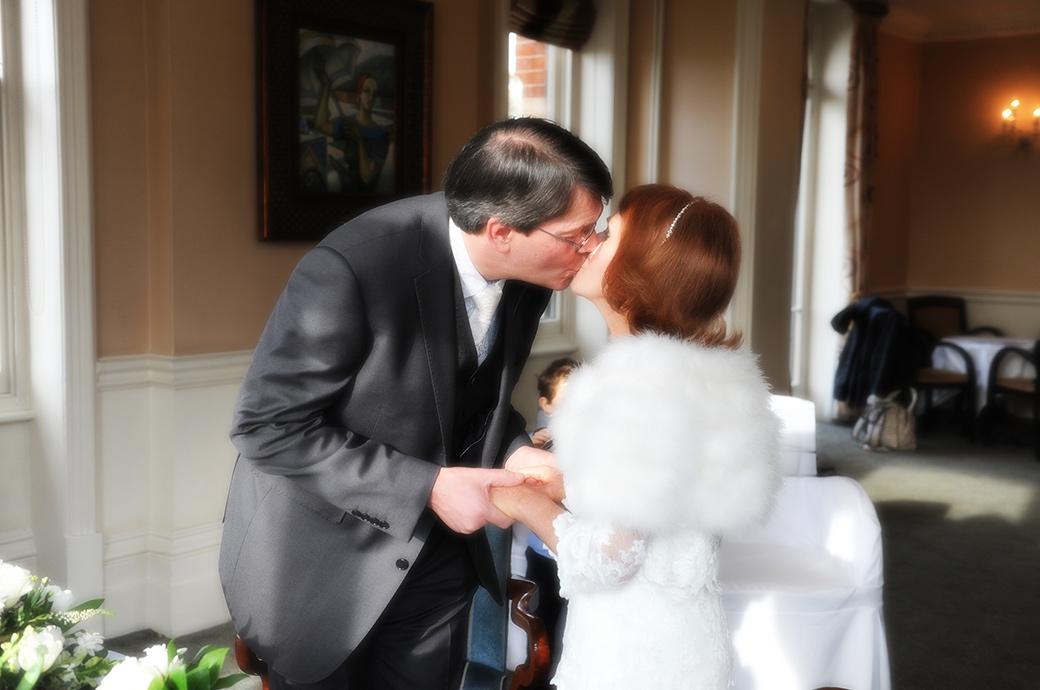 Bride and groom holding hands in the River Room as they kiss after the announcement that they are husband and wife at The Petersham Hotel Surrey wedding venue