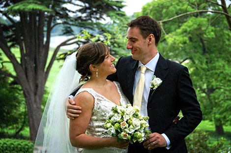 Proud groom holds his wife as they smile into each others eyes out on the lawn at the lovely Petersham Hotel with its wonderful location in Richmond Surrey