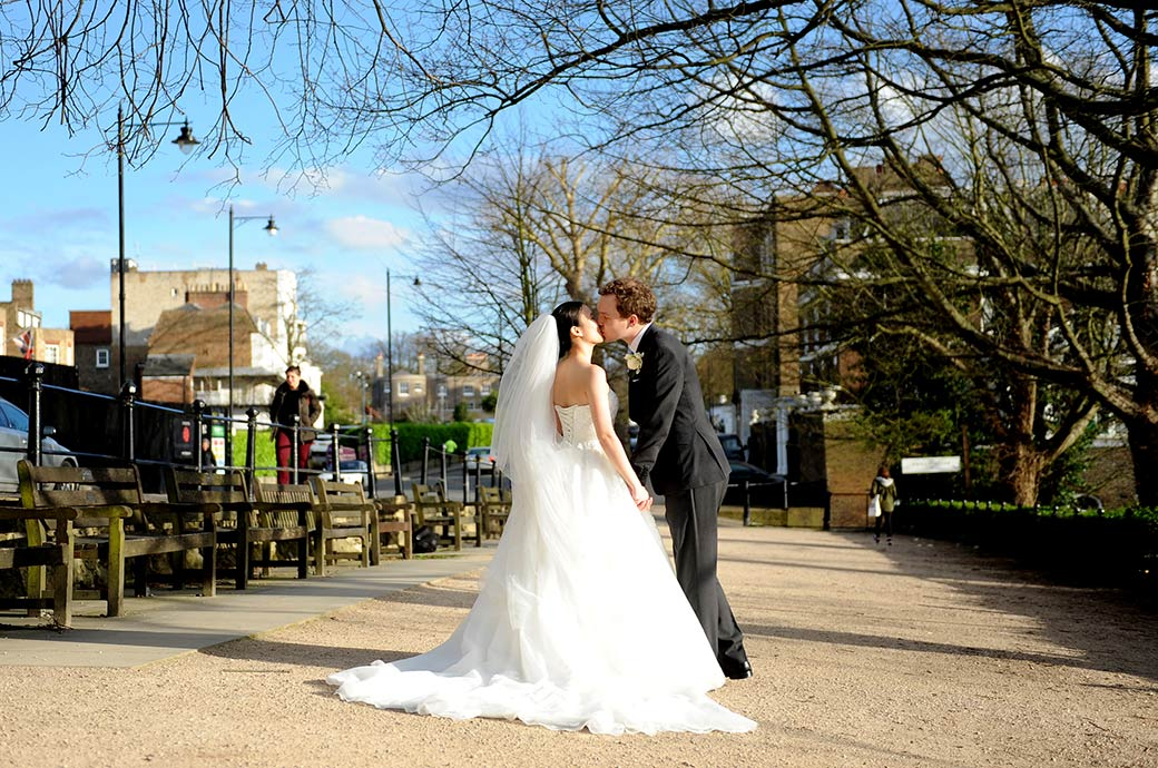 Young lovers after getting married at Surrey wedding venue The Petersham Hotel romantically kiss on the famous Terrace with a view on Richmond Hill