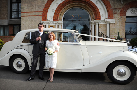 Elegant wedding photograph of a newlywed couple standing together in front of a classic white Rolls Royce outside the beautiful Surrey wedding venue The Petersham Hotel