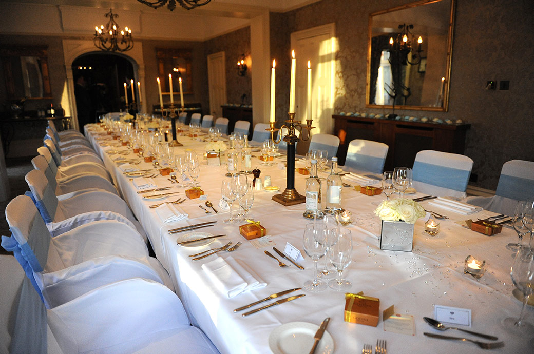 The candles have been lit in the Terrace Room at The Petersham Hotel in Richmond Surrey dressed for the wedding breakfast and awaiting the arrival of the guests