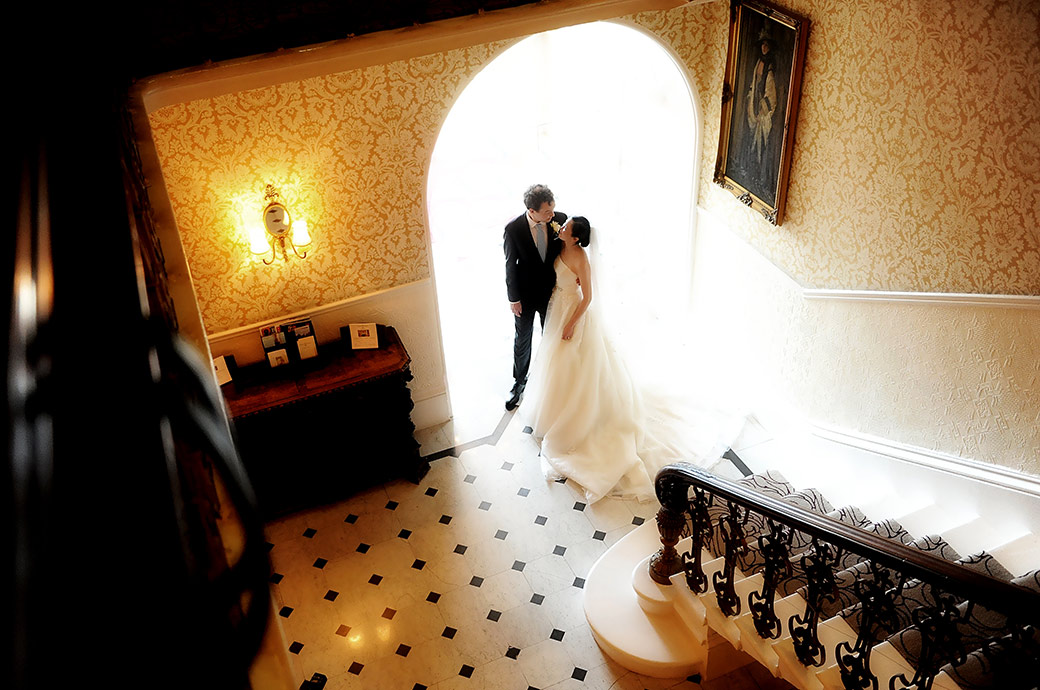 Beautifully romantic wedding photograph of the Bride and groom standing in the doorway at the bottom of the staircase at The Petersham Hotel in Richmond Surrey