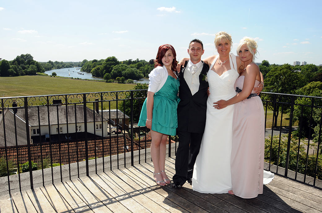 Close family wedding photograph of a Bride and groom with their daughters on the balcony of The Petersham Hotel with a wonderful view behind them of the meandering Thames
