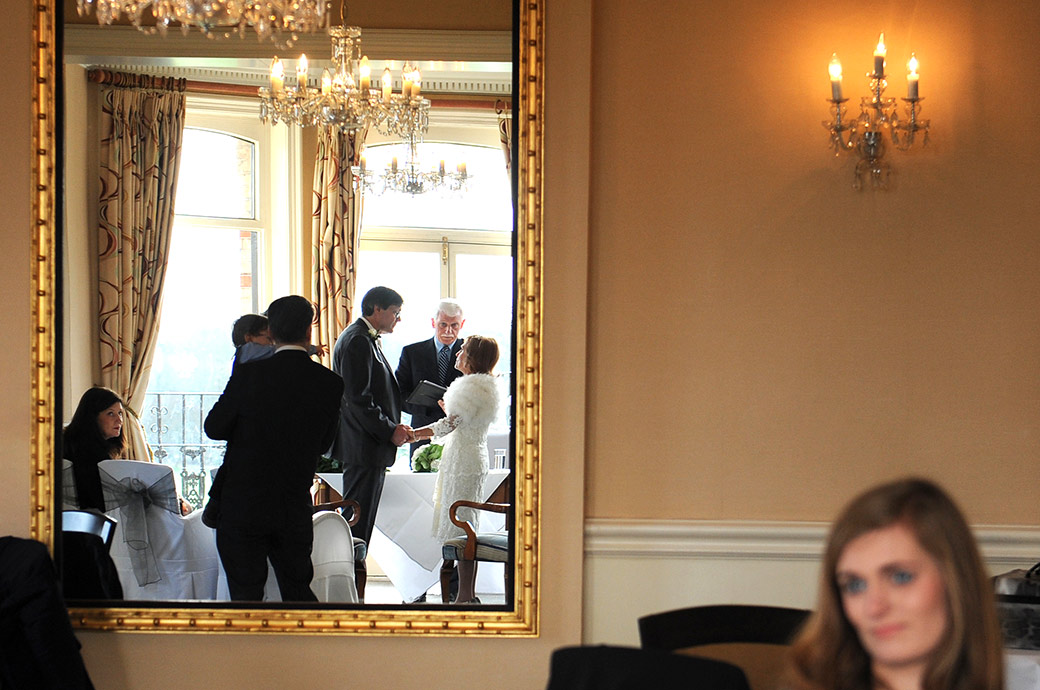 Unusual wedding picture captured in a mirror of the marriage ceremony in the River Room at The Petersham Hotel wedding venue in Richmond Surrey