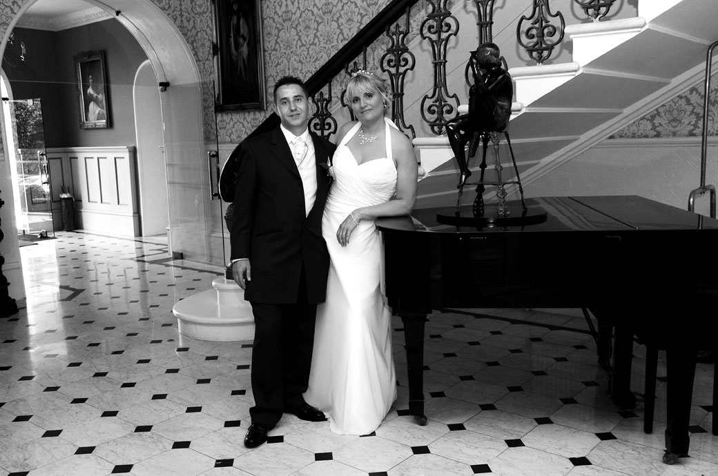 Lovely romantic wedding photograph of the Bride and Groom by the piano at the grand hallway at The Petersham, Surrey wedding venue in Richmond