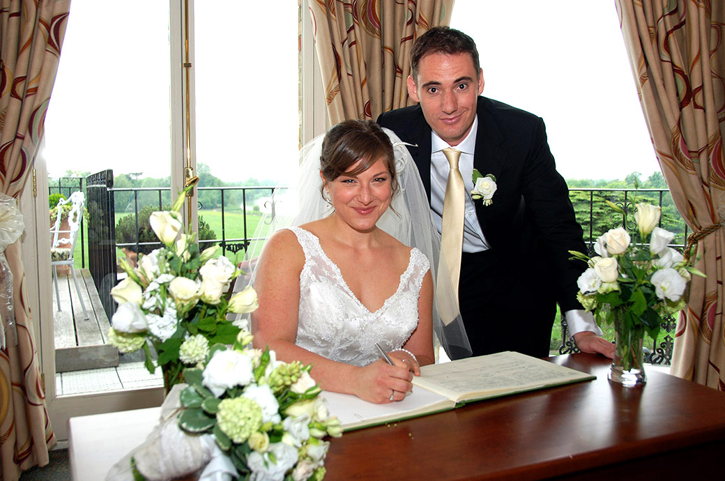 Smiling Bride and groom pose for the Surrey Lane wedding photographer as they sign the marriage register in the River Room at The Petersham Hotel in Richmond