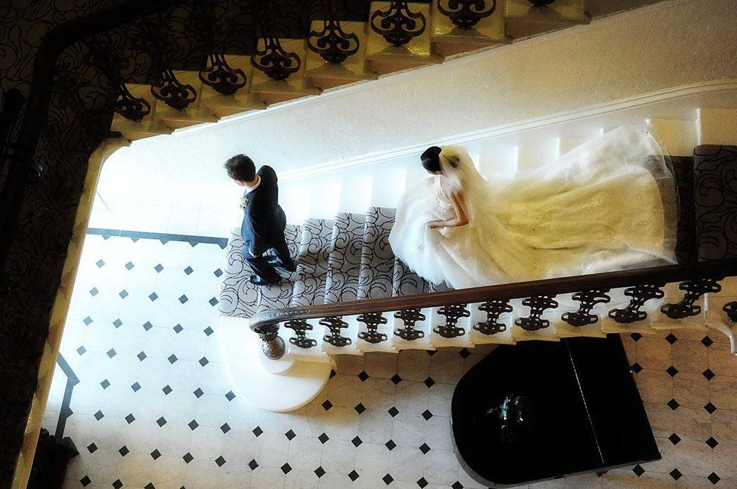 Dramatic and evocative wedding picture taken at Surrey wedding venue The Petersham Hotel of the Bride and groom descending the staircase