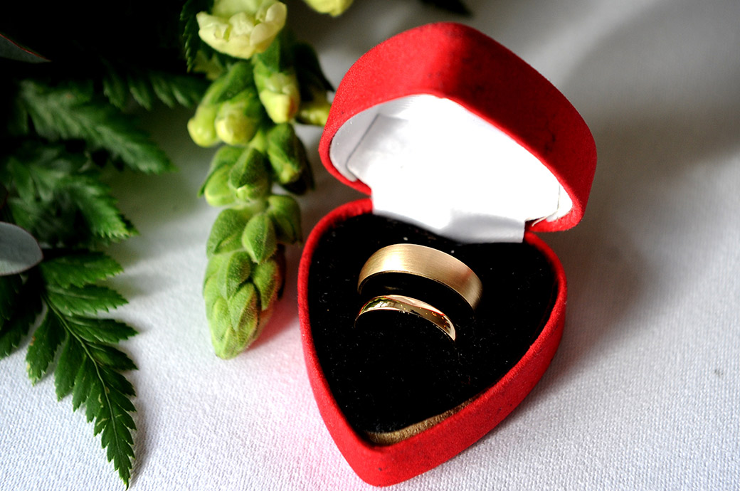 Gold wedding rings sitting in a heart shaped red box captured by a Surrey Lane wedding photographer at The Petersham Hotel Richmond Surrey and looking down over The Thames river