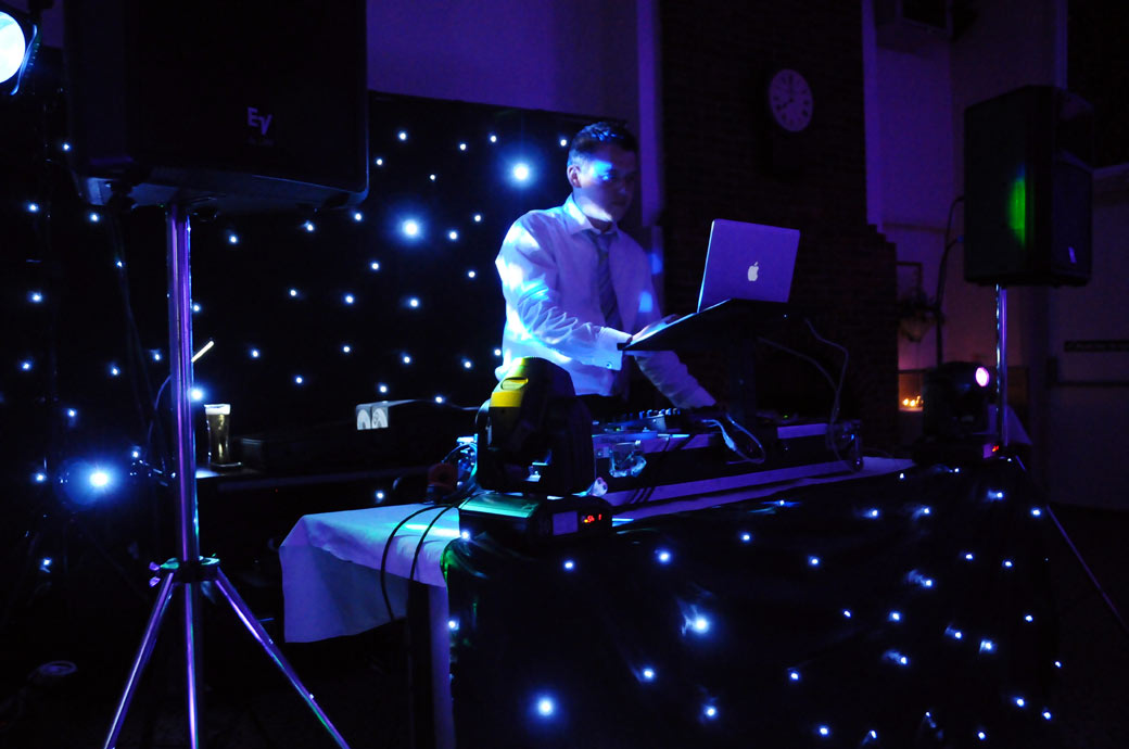 Atmospheric DJ on the decks wedding photograph at the historic Talbot Inn Ripley, a Surrey wedding venue captured by Surrey Lane wedding photography