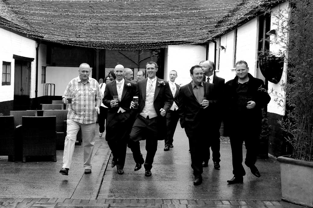 Jolly Groom and his men wedding photo as they walk down the historic courtyard, drinks in hand at the charming Surrey wedding venue The Talbot, Ripley