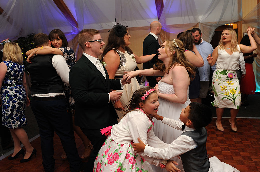 The bride and groom in The London Room at Surrey wedding venue Warren House in Kingston sing and dance on a packed and lively dance floor with their guests