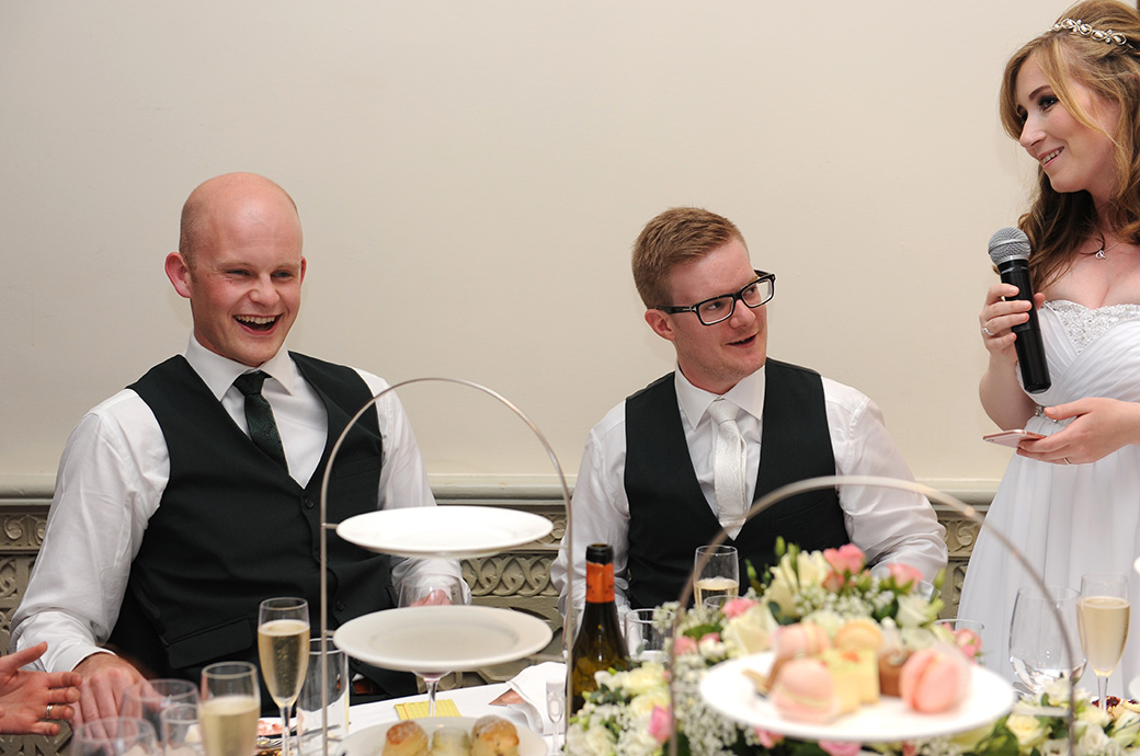Best man laughs and the Groom looks uneasy during the Bride's wedding speech captured in Surrey at Warren House Kingston in the Persian Dining Room