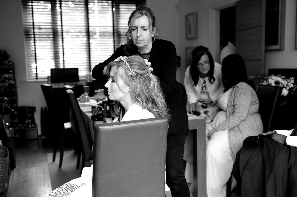 Bride captured at the busy and full family home having her hair done prior to her marriage at the popular Surrey wedding venue in Kingston the lovely Warren House