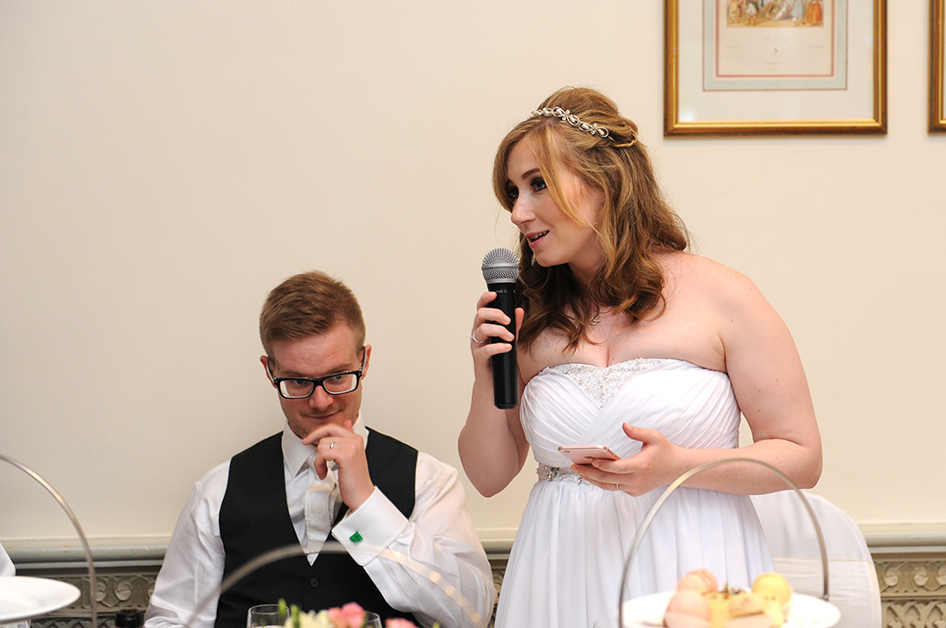 Bride with microphone in hand reveals all in a funny and engaging wedding speech captured at Warren House in Kingston Surrey in the light and airy Persian Dining Room