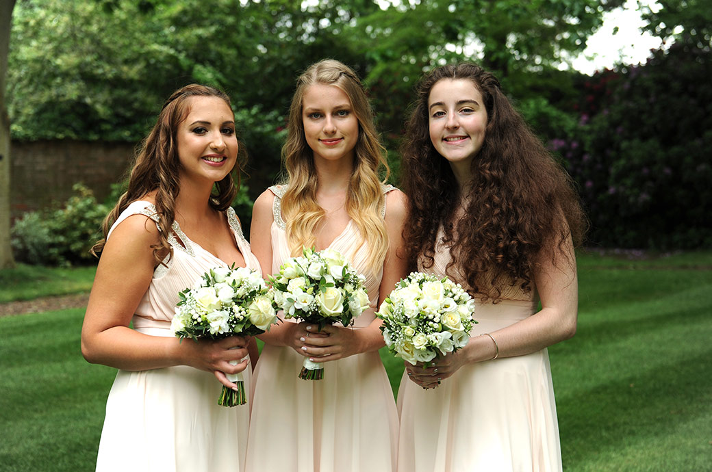 Lovely smiling bridesmaids standing on the lawn and posing with their bouquets at Warren House  in Kingston Upon Thames for the Surrey Lane wedding photographers