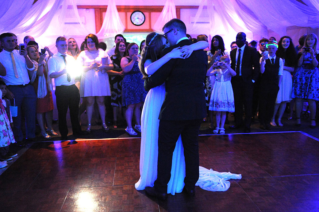 Bride hugs her groom as he kisses her during their first dance in The London Room at the relaxed Warren House a grand but informal wedding venue in Kingston Surrey