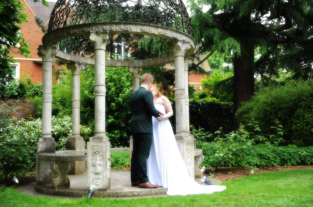Lovely romantic wedding picture of a young Bride and Groom at the renowned Kingston wedding venue Warren House in Surrey standing beneath the stone gazebo kissing