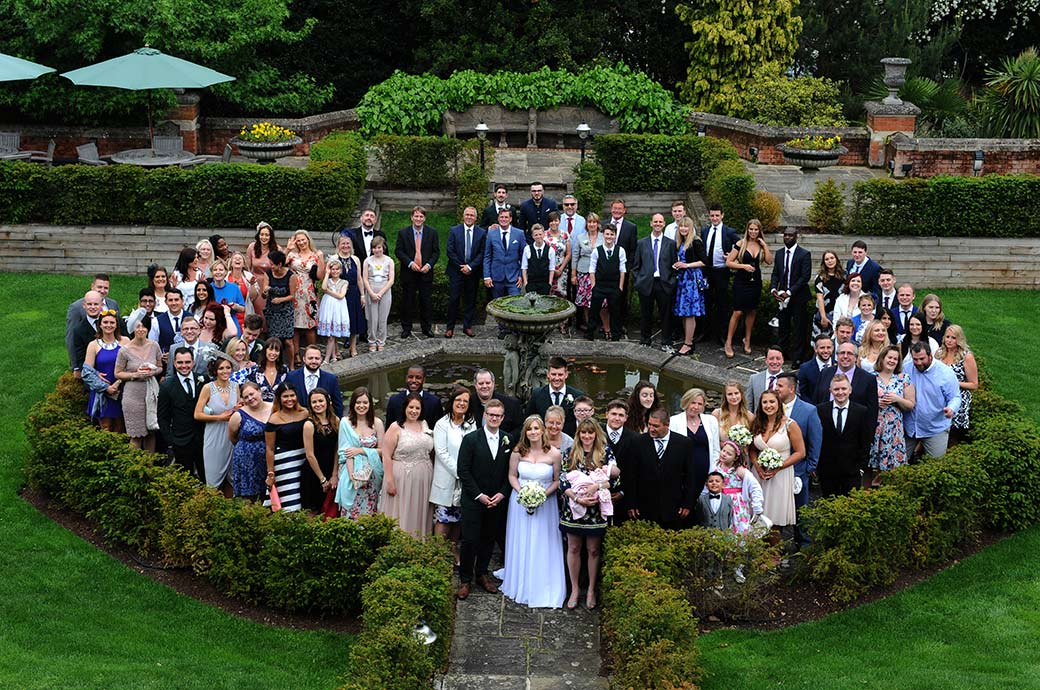 Everyone at a Warren House wedding in Kingston Surrey captured from two floors up as they stand around the ornate Victorian water fountain for the large group wedding photo