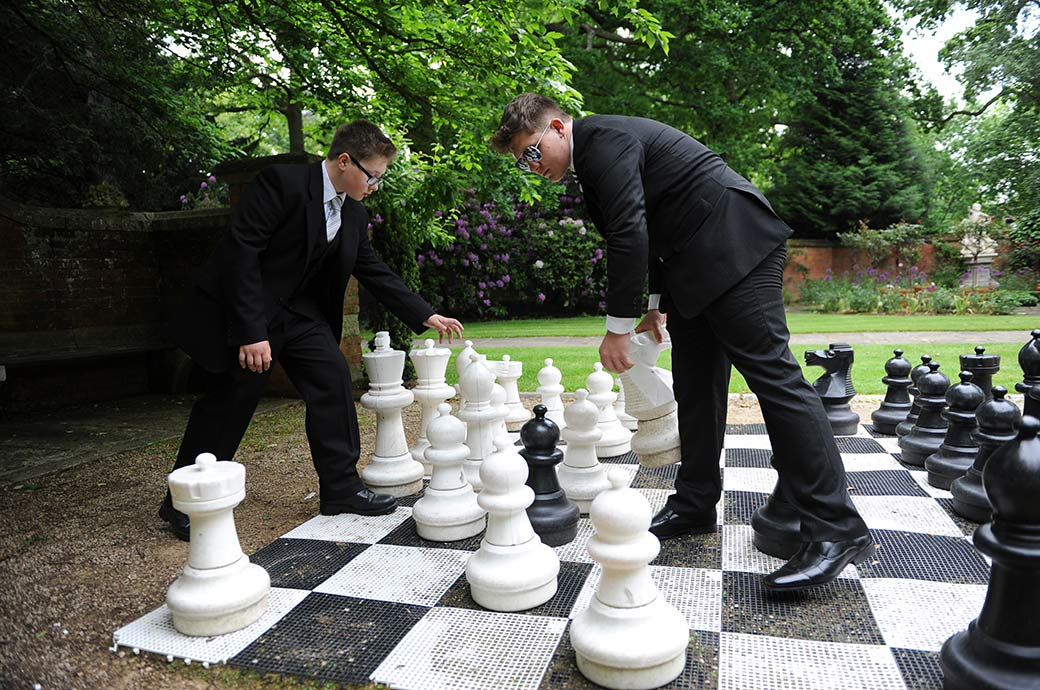 Young wedding guests with their fancy dress sunglasses engrossed in a game of giant chess captured at Surrey wedding venue Warren House in the tranquil landscaped gardens