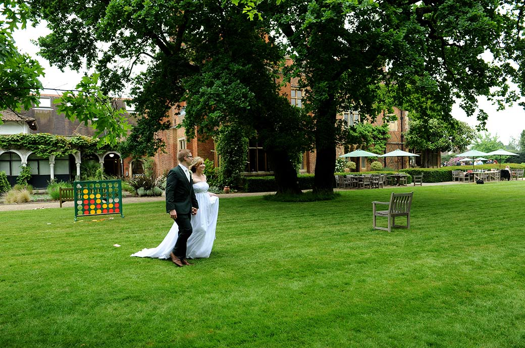 Bride looks happy as she walks along the lawn with the Groom at Surrey wedding venue Warren House in Kingston Upon Thames in this relaxed informal wedding photograph