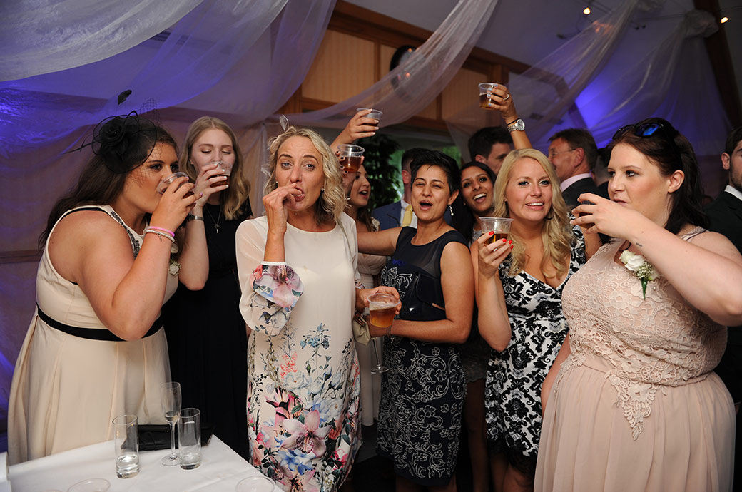 Revelling lady wedding guests at the popular and relaxed Surrey wedding venue Warren House down their Tequila shots as they kick off the night's celebrations in The London Room