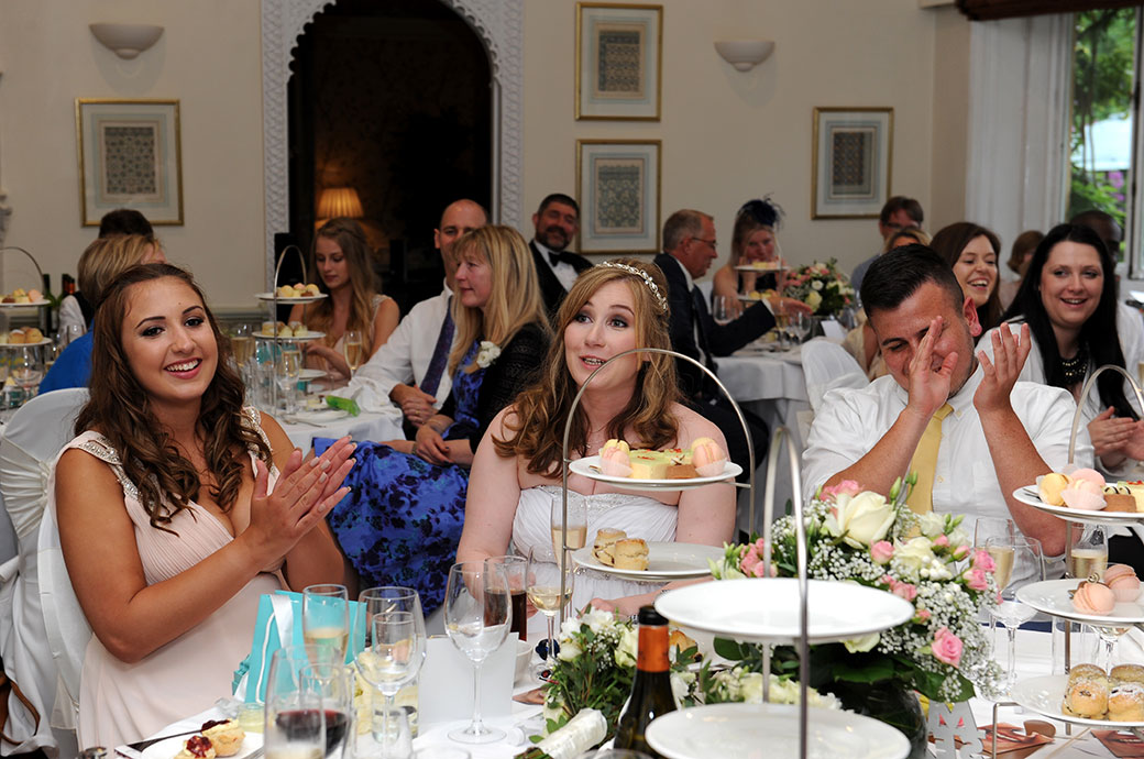 Laughter and applause captured in this wedding photograph taken in the Persian Dining Room at Warren House in Kingston Surrey during the wedding speeches