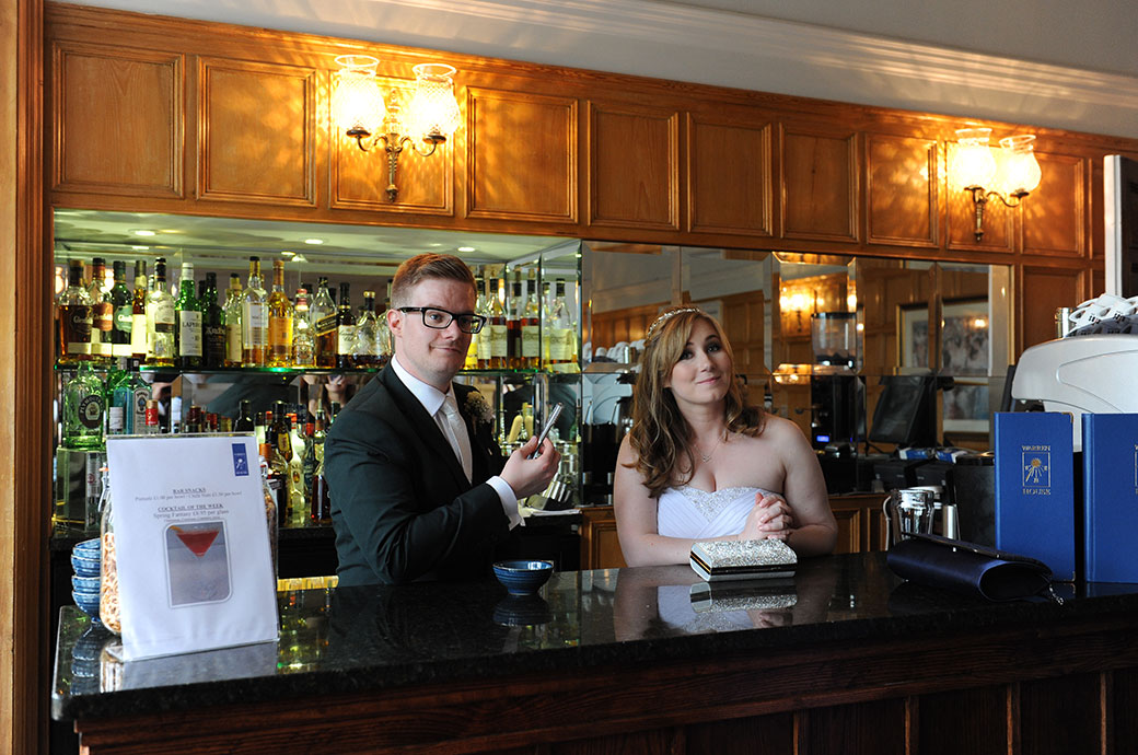 Bride and groom captured in this wedding photograph having fun as they pose behind the bar at Warren House in Kingston a hidden gem of a Surrey wedding venue