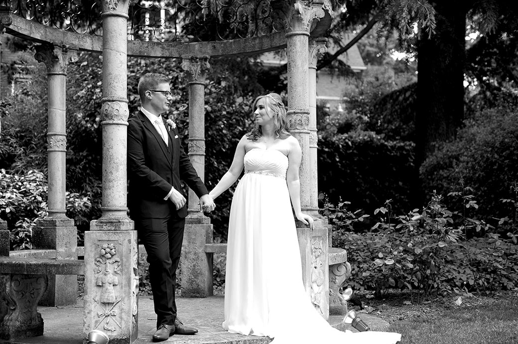Bride at Surrey wedding venue Warren House in Kingston Upon Thames looks lovingly at her Groom as they hold hands standing by the stone gazebo in the large landscaped gardens