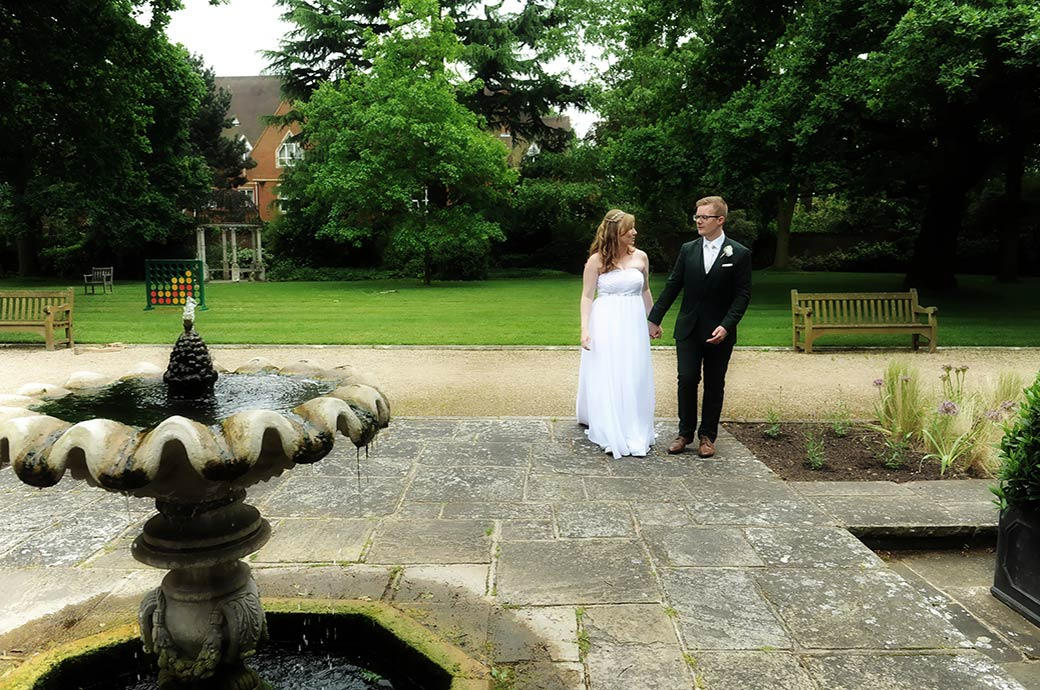Relaxed happy newlyweds couple walking hand in hand towards a small water fountain at the tranquil gem of wedding venue Warren House in Kingston Upon Thames Surrey
