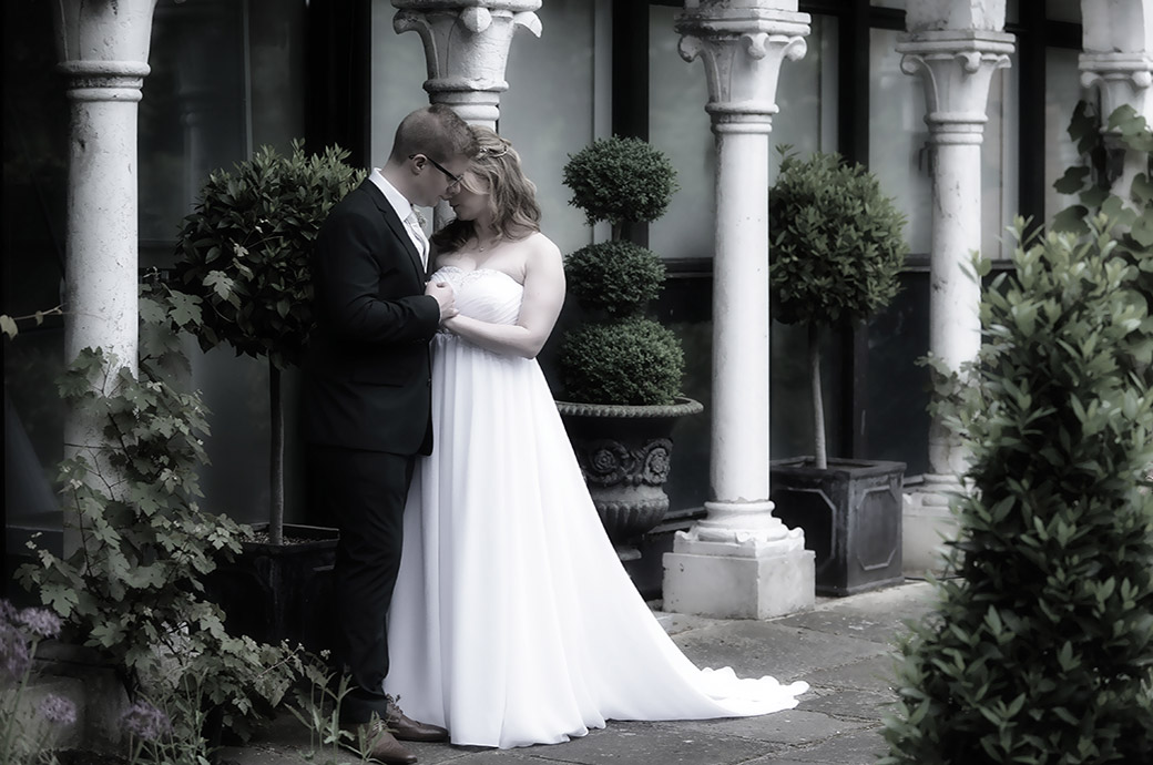 Touching  and romantic moment captured by some white pillars at the Kingston based wedding venue Warren House in Surrey as the Bride and Groom enjoy some moments together