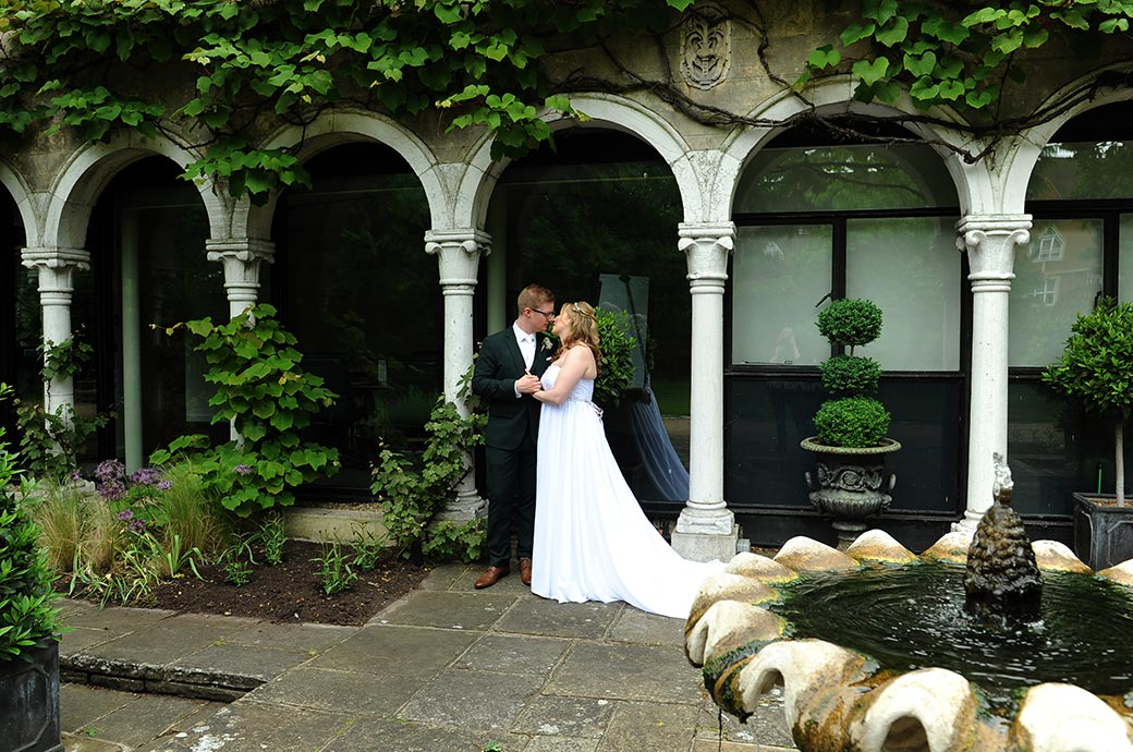 Bride and groom spend a special moment together holding hands by some white pillars near a fountain in the Warren House gardens in Kingston Upon Thames in Surrey