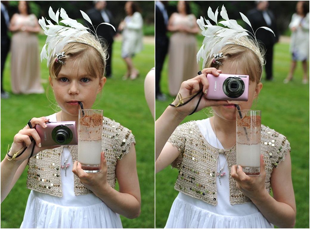 Fun wedding photographs of a little girl drinking her soft drink with a straw whilst taking a picture of the Surrey Lane wedding photographer at the relaxing Warren House in Kingston