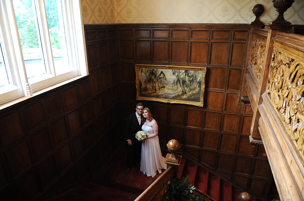 Newlywed couple captured in this relaxed wedding picture standing on the first floor of the magnificent wooden staircase at Warren House in Kingston Surrey with their heads together