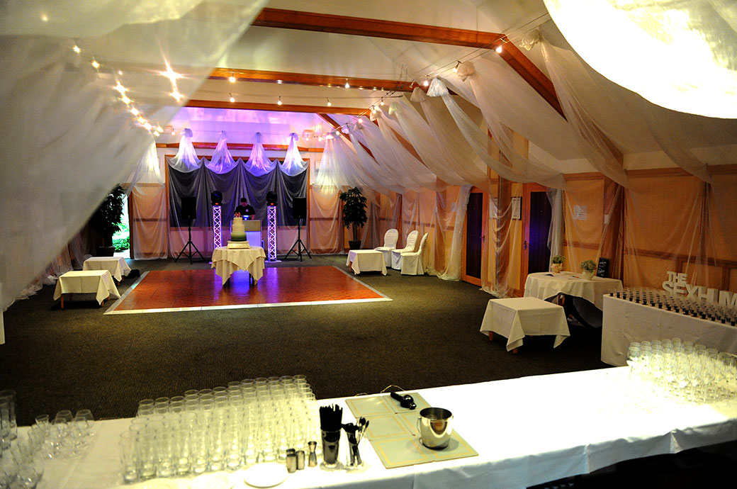 A view from over the bar and wedding cake onto the dancefloor captured at the Surrey wedding venue in Kingston Warren House in Kingston before The London Room celebrations