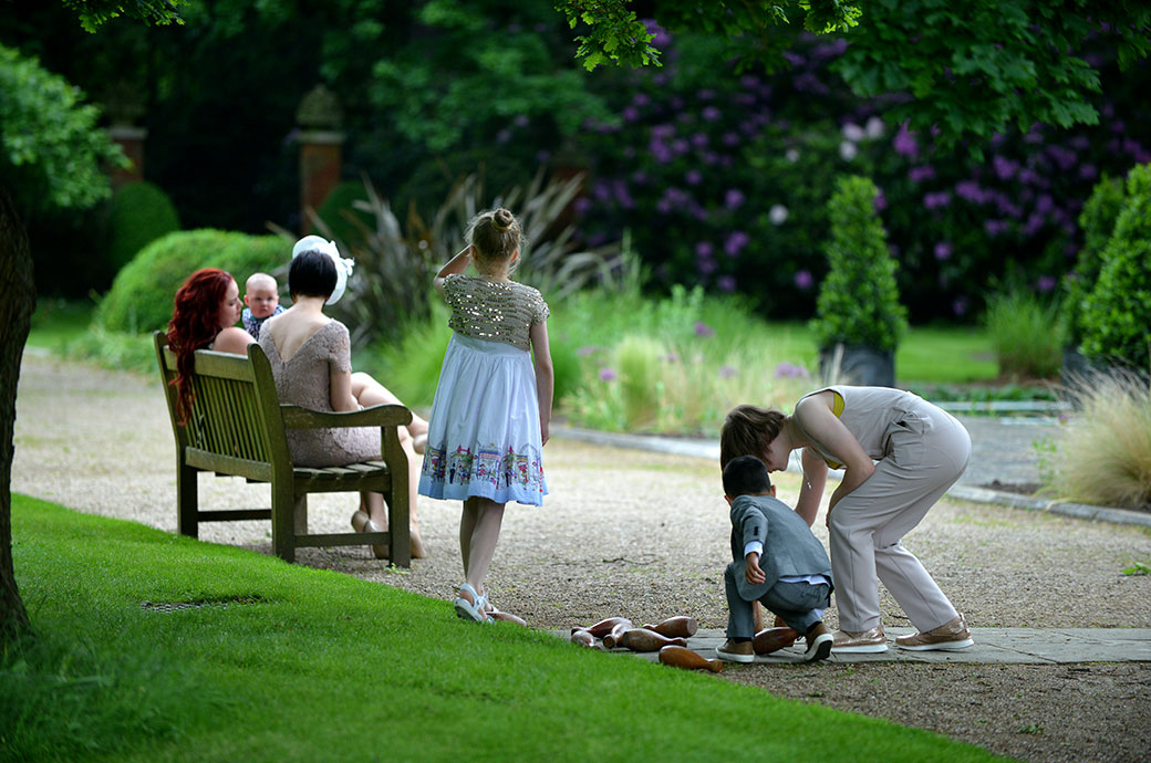 Tranquil scene of children playing skittles as a mother sits with her baby on a garden bench during the drinks reception at Warren House a lovely wedding venue in leafy Surrey